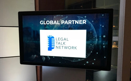 Legal Talk Network's logo on a TV at the Global Legal Hackathon
